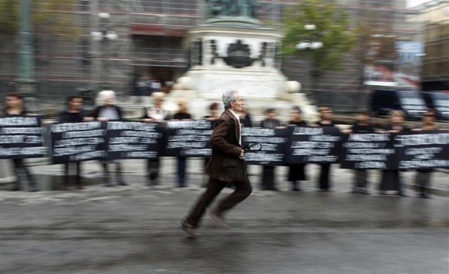 A man runs as protestors hold placards marking the 20th anniversary of the start of the Bosnian war in Belgrade April 6, 2012.