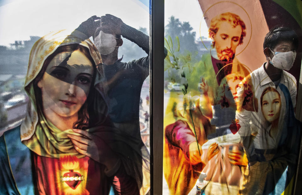 Indian Christian boys wearing face masks as a precaution against the coronavirus peep through the glass of the church as they are not allowed to attend the Christmas mass due to COVID-19 restrictions in Gauhati, India, Friday, Dec. 25, 2020. (AP Photo/Anupam Nath)