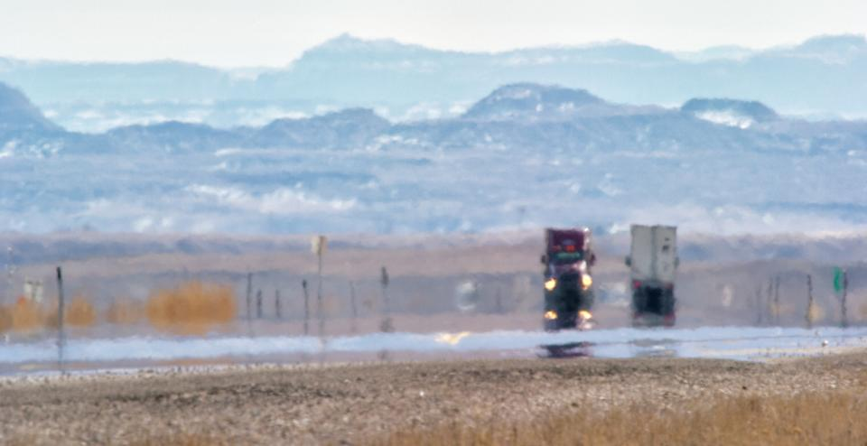 Heat Haze Distorts Video of Semi-Trucks Driving Down a Utah Interstate Surrounded by Mountains on a Sunny Day