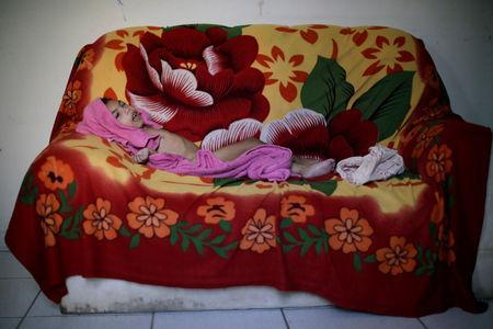 Luana Vieira, who is two years old, and was born with microcephaly, lies on a sofa after bath at her house in Olinda, Brazil, August 6, 2018. REUTERS/Ueslei Marcelino/Files