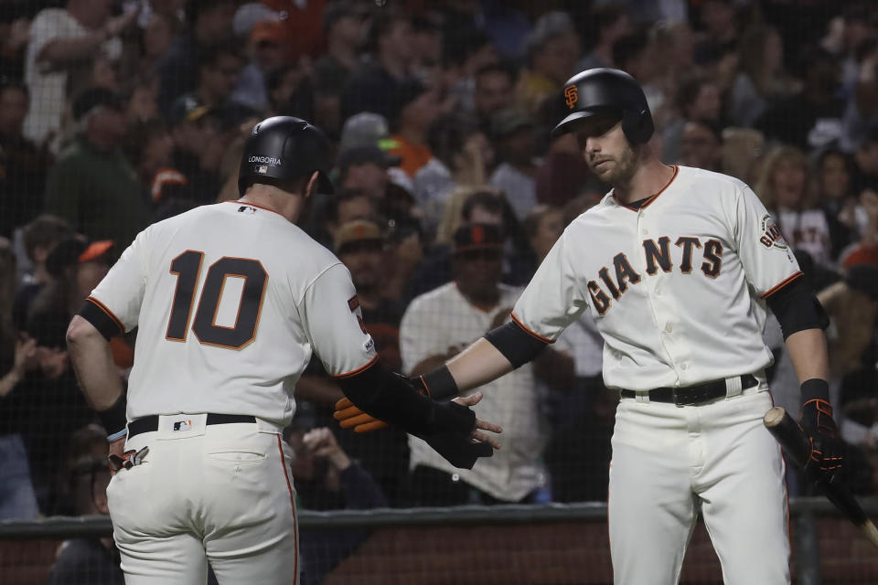 San Francisco Giants' Evan Longoria (10) is congratulated by Austin Slater after scoring against the Oakland Athletics during the sixth inning of a baseball game in San Francisco, Tuesday, Aug. 13, 2019. (AP Photo/Jeff Chiu)