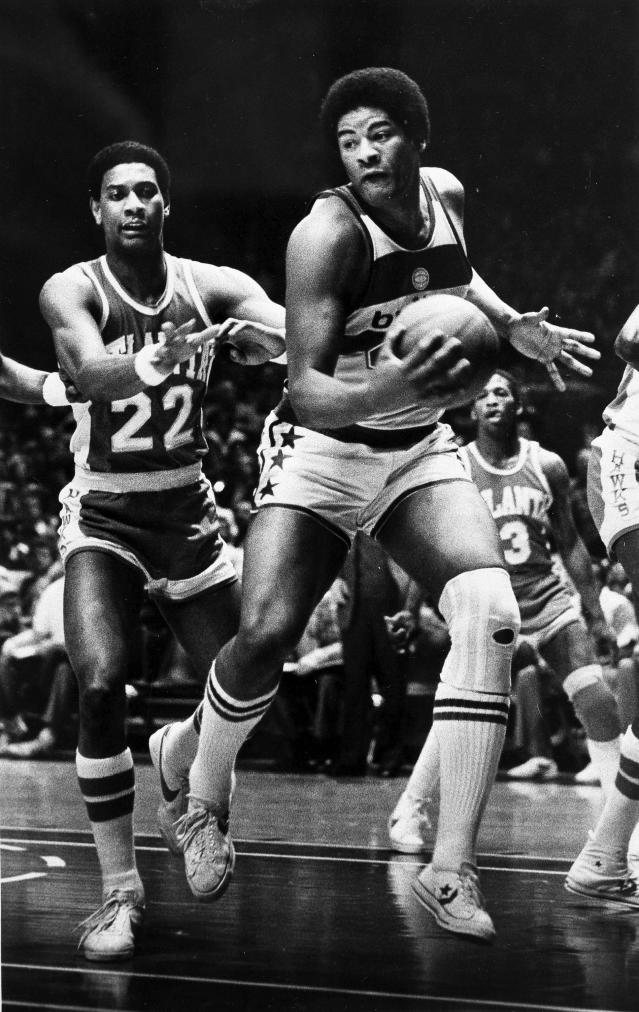 FILE - In this Jan . 30, 1979, file photo, Wes Unseld of the Washington Bullets takes in an offensive rebound against John Drew (22) of the Atlanta Hawks during the first half of an NBA basketball game in Landover, Md. Unseld, the workmanlike Hall of Fame center who led Washington to its only NBA championship and was chosen one of the 50 greatest players in league history, died Tuesday, June 2, 2020, after a series of health issues, most recently pneumonia. He was 74. (AP Photo/FIle)