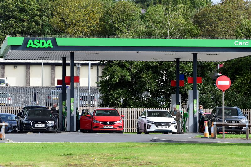 Cars wait at a petrol and diesel filling station in Pembroke Dock