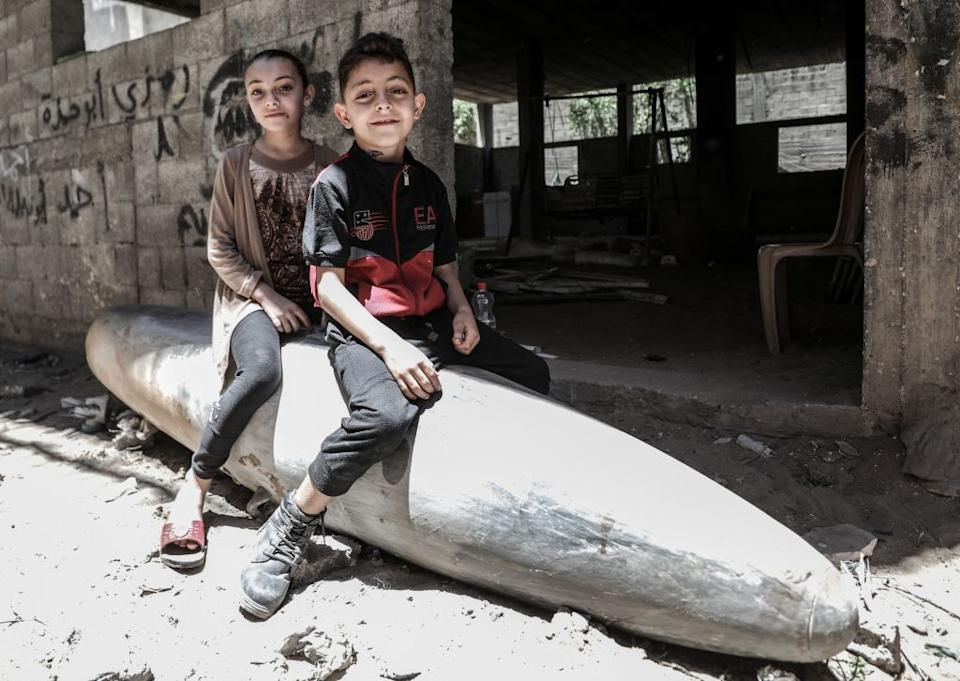 Gazan children sitting onto an unexploded missile thrown by Israeli forces in al-Rimal neighbourhood on May 18, 2021.