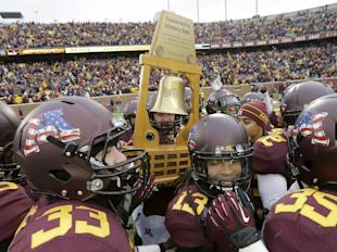 Minnesota Players carry the Governor's Victory Bell trophy after beating Penn State in 2013. (AP)