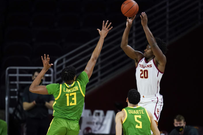Southern California guard Ethan Anderson (20) shoots against Oregon forward Chandler Lawson (13) and guard Chris Duarte (5) during the first half of an NCAA college basketball game Monday, Feb. 22, 2021, in Los Angeles. (AP Photo/Ashley Landis)