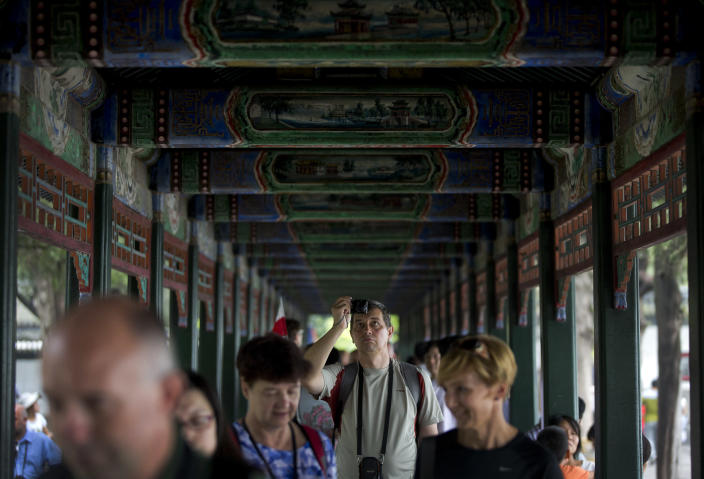 "In this Wednesday, Aug. 28, 2013 photo, a tourist takes pictures as he and others walk down a corridor adorned with thousands of paintings depicting landscapes, birds and flowers at the Summer Palace in Beijing. China's new tourism slogan ""Beautiful China"" has been criticized by industry experts who say it illustrates a marketing problem that has led to a weakness in growth in foreign visitors over the past few years. (AP Photo/Andy Wong)"