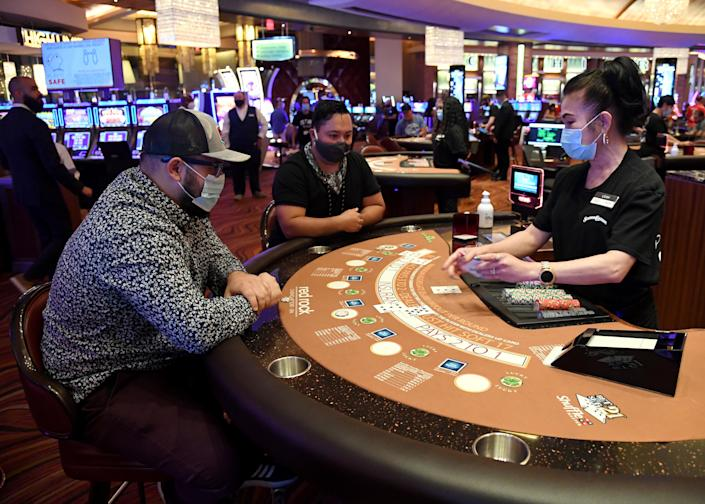 Locals Evan Savar and Nabu Reyes play blackjack with dealer Leah Prerost at the Red Rock Resort after the property opened for the first time since being closed on March 17 because of the coronavirus (COVID-19) pandemic, on June 4, 2020 in Las Vegas, Nevada. (Photo by Ethan Miller/Getty Images)