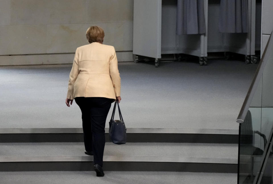 File - In this Tuesday, Sept. 7, 2021 file photo, German Chancellor Angela Merkel leaves the plenary hall after a debate about the situation in Germany ahead of the upcoming national election in Berlin, Germany. Angela Merkel, Germany's first female chancellor, has been praised by many for her pragmatic leadership in a turbulent world and celebrated by some as a feminist icon but she wouldn't seek reelection in the country's Sept. 26 general election. (AP Photo/Markus Schreiber, File)