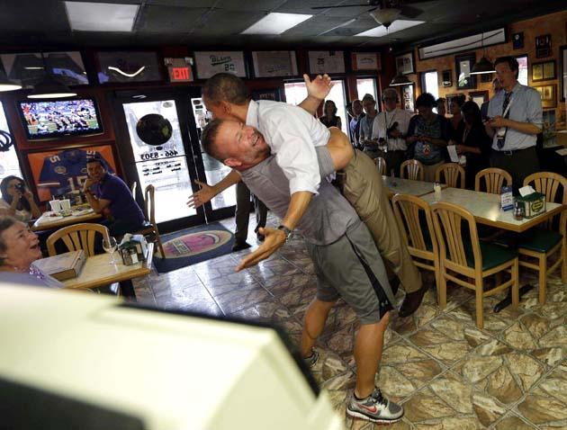 President Barack Obama, right, is picked up and lifted off the ground by Scott Van Duzer, left, owner of Big Apple Pizza and Pasta Italian Restaurant during an unannounced stop in Ft. Pierce, Fla., Sept. 9, 2012. (Pablo Martinez Monsivais / AP Photo)