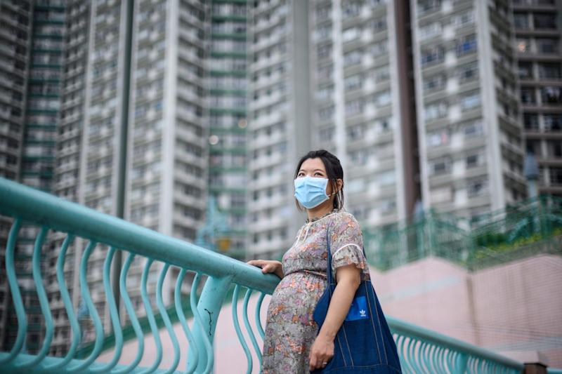In this picture taken on March 31, 2020, expectant mother Jamie Chui, 33, poses in front of residential buildings near where she lives in Hong Kong. - Jamie Chui has been a virtual prisoner in her Hong Kong home for most of her nine-month pregnancy. Trapped intially by violent pro-democracy protests and tear gas, and then by the coronavirus -- she now faces giving birth alone, with her husband unlikely to see his child until days later. (Photo by Anthony WALLACE / AFP) / TO GO WITH Hong Kong-China-Indonesia-Philippines-health-virus-pregnancy, FOCUS by Liz THOMAS, Yan ZHAO (Photo by ANTHONY WALLACE/AFP via Getty Images)