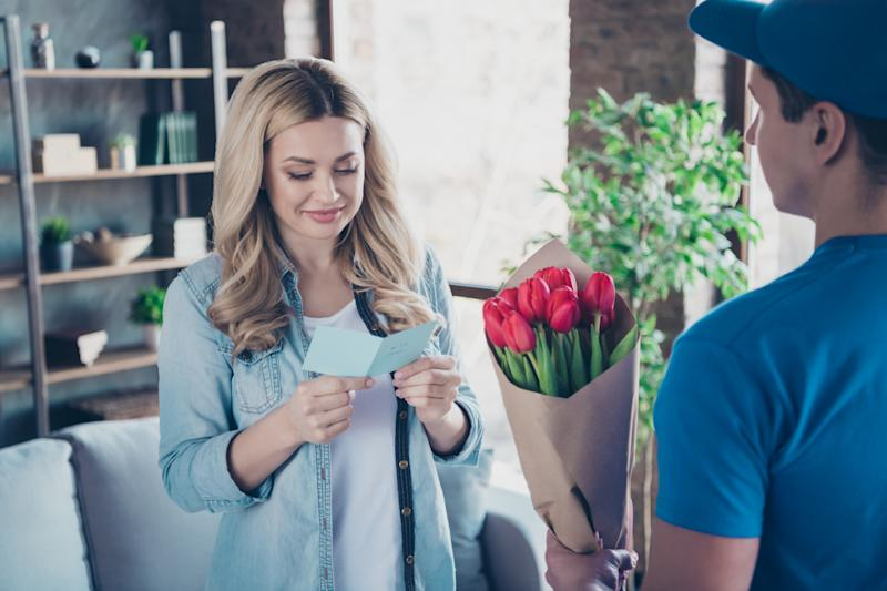 Portrait of nice attractive charming lovable pretty cheerful cheery wavy-haired girl receiving, congrats card greetings red flowers at modern industrial loft brick style interior room indoors