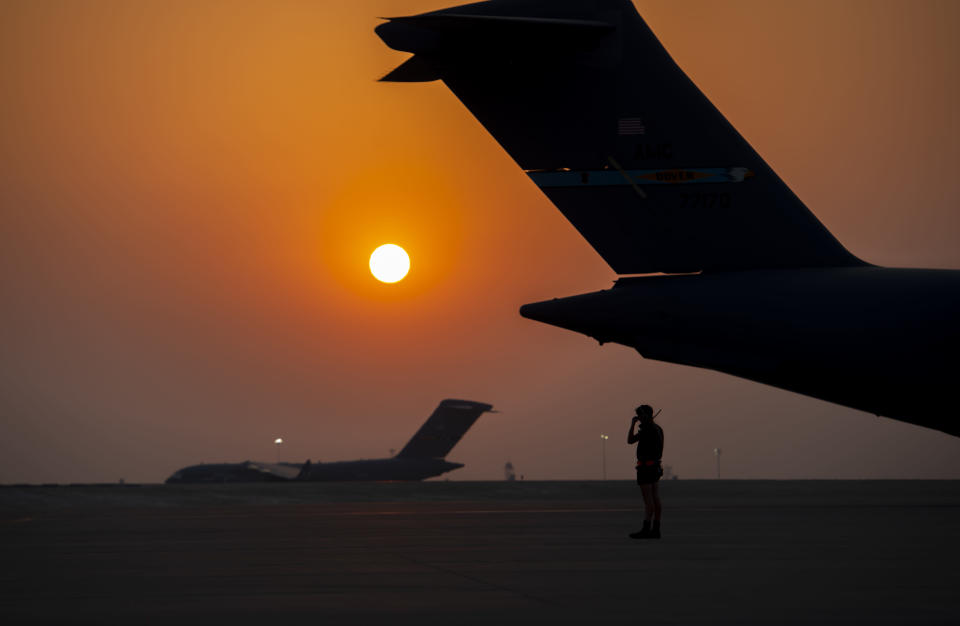 In this image provided by the U.S. Air Force, a member from the 379th Air Expeditionary Wing prepares to marshal a C-17 Globemaster lll Aug. 23, 2021, at Al Udeid Air Base, Qatar. (Airman 1st Class Kylie Barrow/U.S. Air Force via AP)
