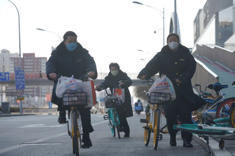 Women wearing face masks ride shared bicycles, as the country is hit by an outbreak of the novel coronavirus, in Beijing