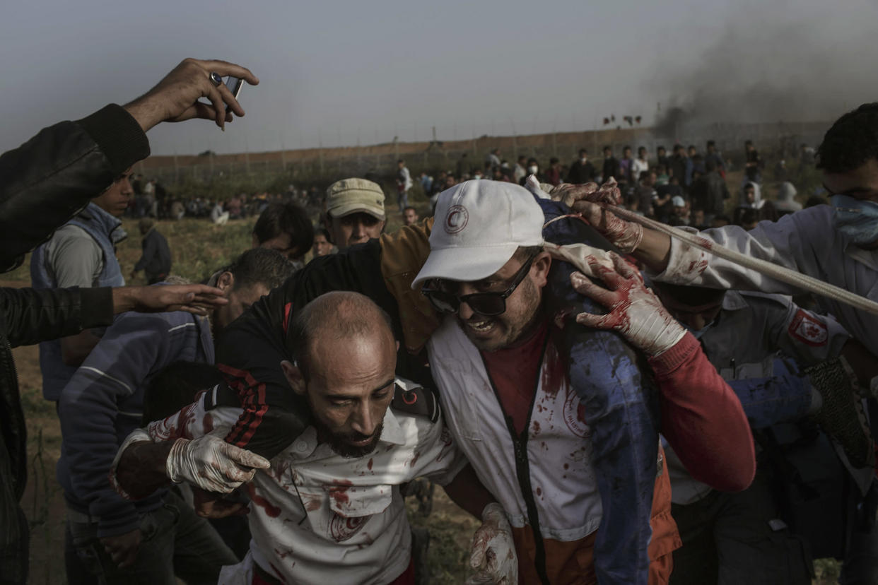 """Palestinian paramedics evacuate a injured man who was shot by an Israeli sniper during the """"Great March of Return"""" protests along the Eastern Gaza City's border on April 13, 2018. (Photo: Fabio Bucciarelli for Yahoo News)"""