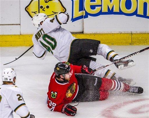 Chicago Blackhawks Jimmy Hayes (39) takes out the legs of Dallas Stars' Ryan Garbutt during the third periods the Stars beat the Chicago Blackhawks 3-1 in an NHL hockey game in Chicago on Thursday, Feb. 23, 2012. (AP Photo/Charles Cherney)