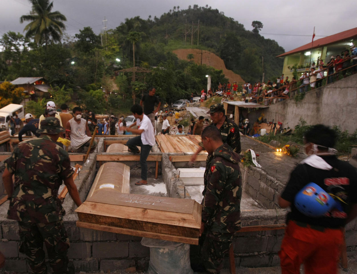 Soldiers carry coffins of flash flood victims during a mass burial Tuesday Dec. 20, 2011 at a public cemetery in Iligan city in southern Philippines. Dozens of grieving relatives of the victims wept openly during funeral rites presided by a Catholic bishop at nightfall in the city. (AP Photo/Bullit Marquez)