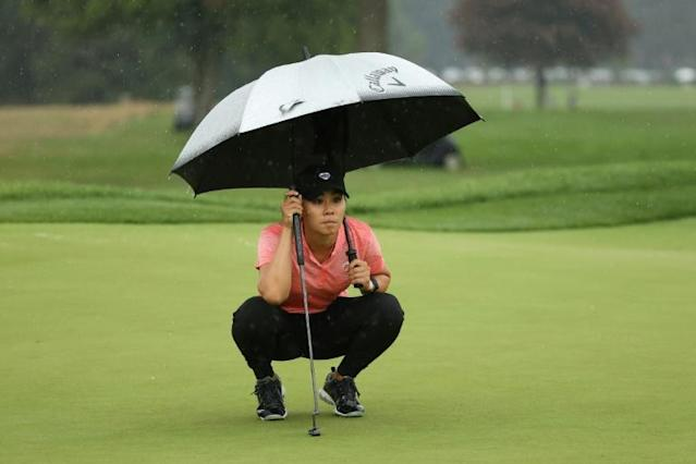 American Danielle Kang lines up a putt under an umbrella Saturday on her way to a one-over par 73 that kept her in a share of the lead at the LPGA Drive On Championship at Inverness Club in Toledo, Ohio (AFP Photo/Gregory Shamus)