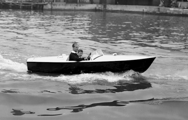Prince Charles with his father the Duke of Edinburgh at the wheel, as they take a motor boat ride up the River Medina at Cowes, Isle of Wight in 1957. (PA Images)