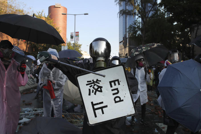 A protestor bangs a metal rod on a street sign during a confrontation at the Hong Kong Polytechnic University in Hong Kong, Nov. 17, 2019. (Photo: Kin Cheung/AP)