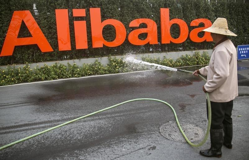 A cleaner waters the flowers below a logo of Alibaba (China) Technology Co. Ltd at the company's headquarters on the outskirts of Hangzhou