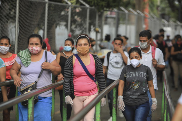Workers wear masks as a protection against the spread of the new coronavirus as they leave from a day's work in Managua, Nicaragua, Monday, May 11, 2020. President Daniel Ortega's government has stood out for its refusal to impose measures to halt the new coronavirus for more than two months since the disease was first diagnosed in Nicaragua. Now, doctors and family members of apparent victims say, the government has gone from denying the disease's presence in the country to actively trying to conceal its spread. (AP Photo/Alfredo Zuniga)
