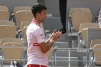 Serbia's Novak Djokovic applauds Italy's Lorenzo Musetti who leaves the court after retiring due to an injury during their fourth round match on day 9, of the French Open tennis tournament at Roland Garros in Paris, France, Monday, June 7, 2021. Djokovic beat 19-year-old Lorenzo Musetti of Italy, who retired with an injury two games from defeat in the fourth round at the French Open. (AP Photo/Michel Euler)