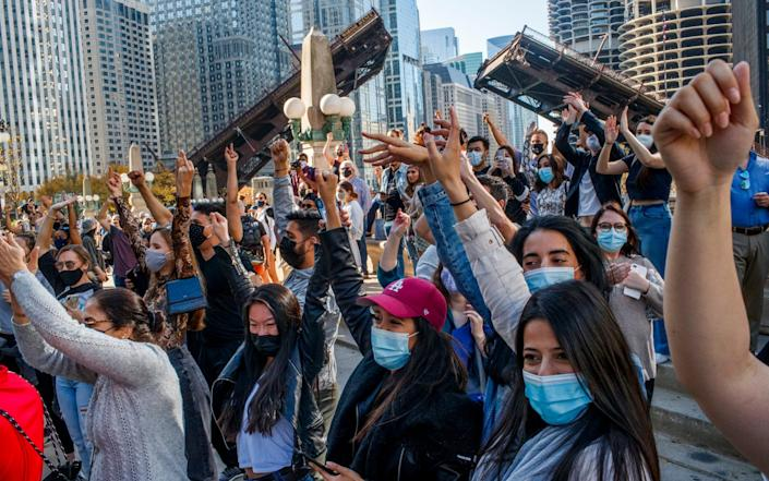 A crowd of mostly young women stand with their fists raised in front of a raised bridge in Chicago - Armando L. Sanchez/Chicago Tribune