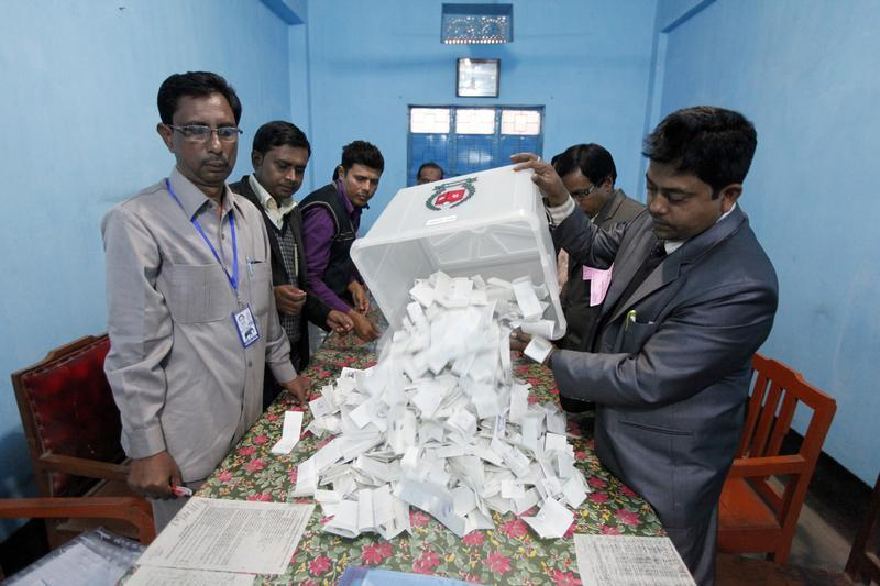 Polling officer pours ballot papers from a box onto a table to count during parliamentary elections in Dhaka