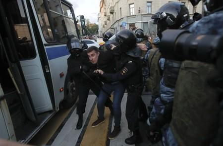 Law enforcement officers detain a man after a rally to demand authorities allow opposition candidates to run in a local election in Moscow