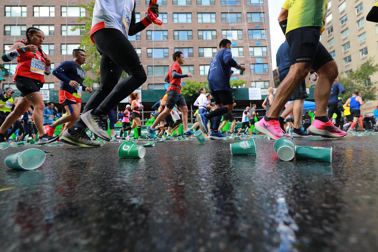 Runners pass discarded cups on First Avenue during the New York City Marathon. (Photo: Gordon Donovan/Yahoo News)