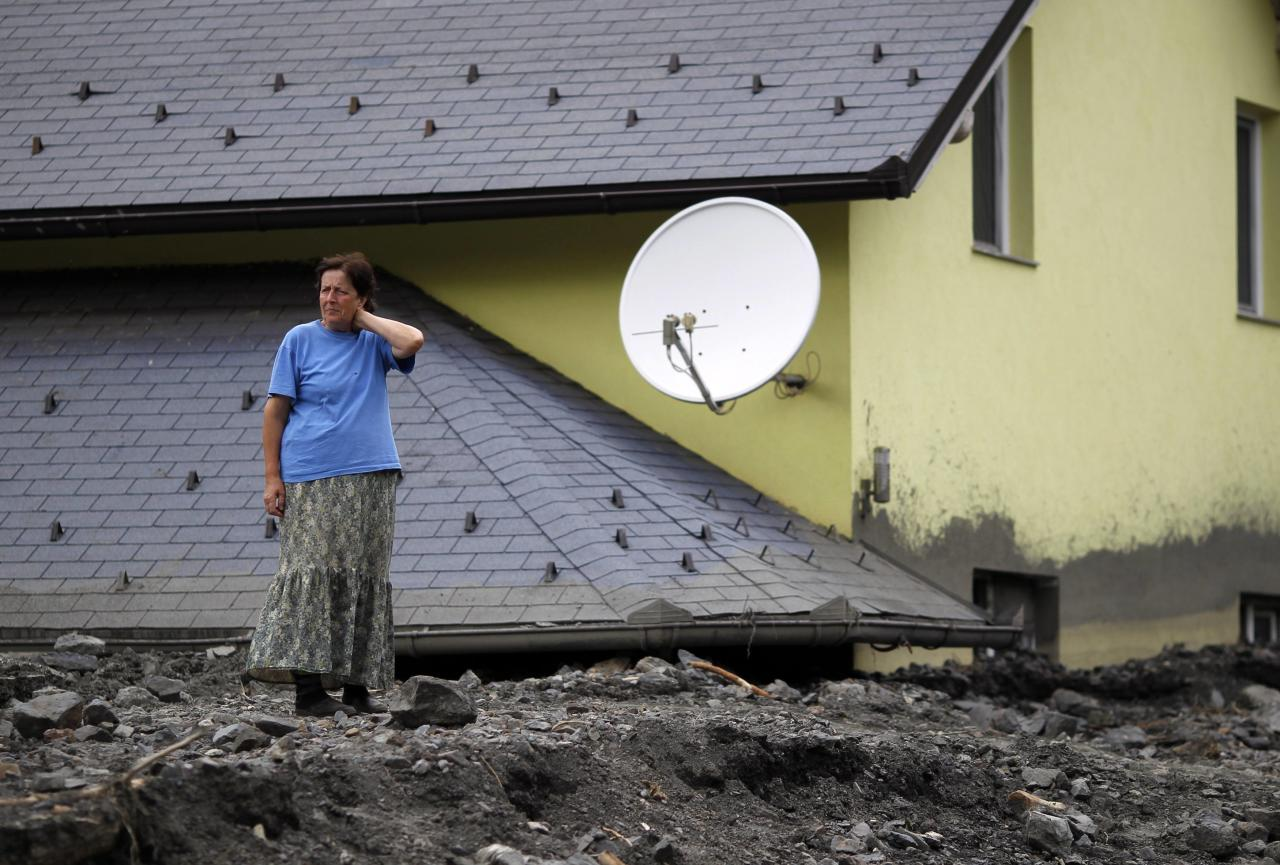A woman stands in front of her flood-damaged house in Topcic Polje May 21, 2014. At least 40 people have died in Serbia, Bosnia and Croatia, after days of the heaviest rainfall since records began 120 years ago caused rivers to burst their banks and triggered hundreds of landslides. REUTERS/Dado Ruvic (BOSNIA AND HERZEGOVINA - Tags: DISASTER ENVIRONMENT)