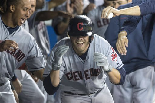 Cleveland Indians' Mark Reynolds celebrates in the dugout after hitting a home run off Toronto Blue Jays' Mark Buehrle during the fourth inning of a baseball game in Toronto on Thursday, April 4, 2013. (AP Photo/The Canadian Press, Chris Young)