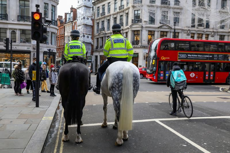 Mounted police and a Deliveroo rider wait at a red light at Regent Street in London