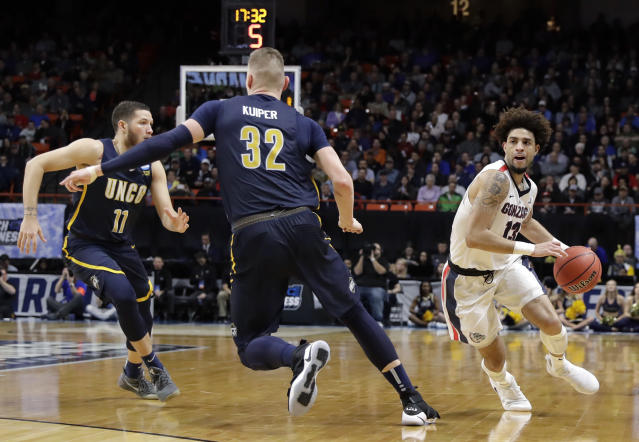 Gonzaga guard Josh Perkins, right, looks to pass around UNC-Greensboro forward Jordy Kuiper (32) during the second half of an NCAA college basketball tournament first-round game, Thursday, March 15, 2018, in Boise, Idaho. (AP Photo/Otto Kitsinger)