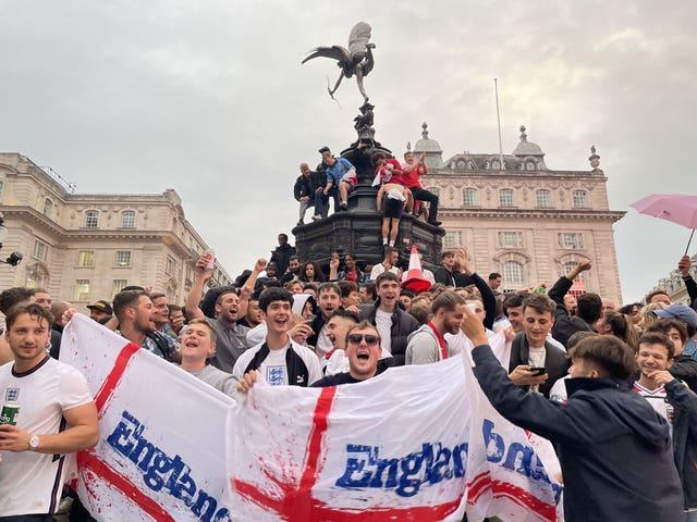 England football fans climb the statue of Eros in Piccadilly Circus, central London, celebrating England's victory over Germany in the Euro 2020 round of 16 match. Picture date: Tuesday June 29, 2021