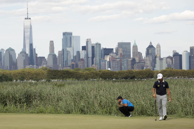With the New York skyline in the distance, Patrick Reed, left, and Abraham Ancer look at their prospective putts on the 14th green at the Northern Trust golf tournament at Liberty National Golf Course, Sunday, Aug. 11, 2019, in Jersey City, N.J. (AP Photo/Mark Lennihan)