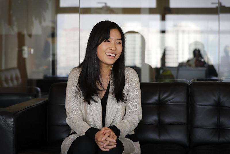 """In this Nov. 16, 2016 photo, Chinese director Zhang Mo smiles during an interview at her office in Beijing. Zhang, the daughter of Chinese cinematic great Zhang Yimou, releases her directorial debut on Dec. 2, 2016. Based on an internet novel, a genre so popular that its fantasy and romance stories have been turned into several films and web series, """"Suddenly Seventeen"""" is about a 28-year-old woman who goes back in time to when she was 17. (AP Photo/Andy Wong)"""