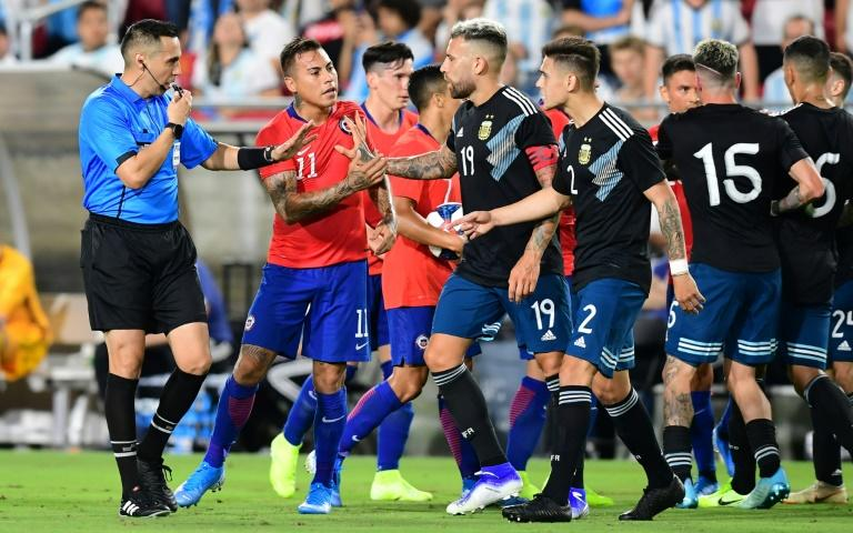 Eduardo Vargas of Chile argues with Argentina's Nicolas Otamendi as the referee intervenes during their international friendly football at LA Memorial Coliseum