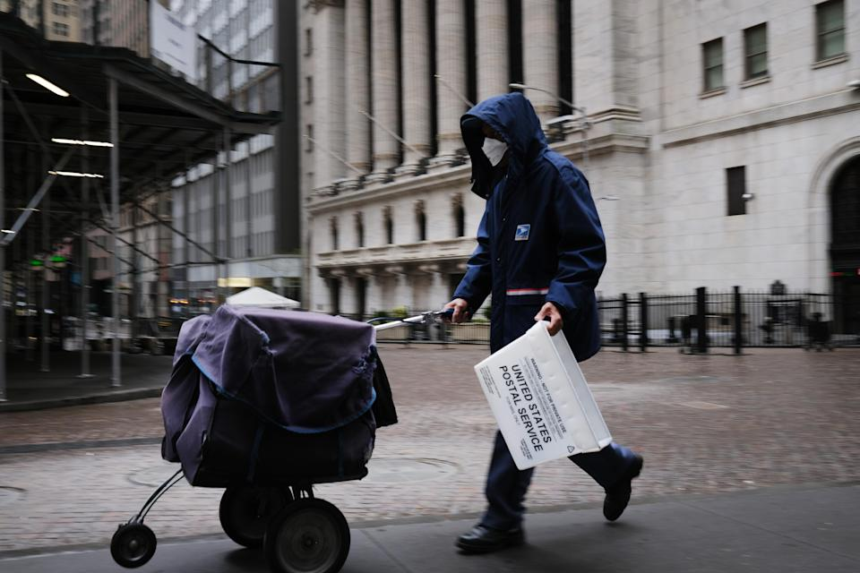 A mail carrier walks along Wall Street as the coronavirus keeps financial markets and businesses mostly closed on May 08, 2020 in New York City. The Bureau of Labor Statistics announced on Friday that the US economy lost 20.5 million jobs in April. (Photo: Spencer Platt/Getty Images)