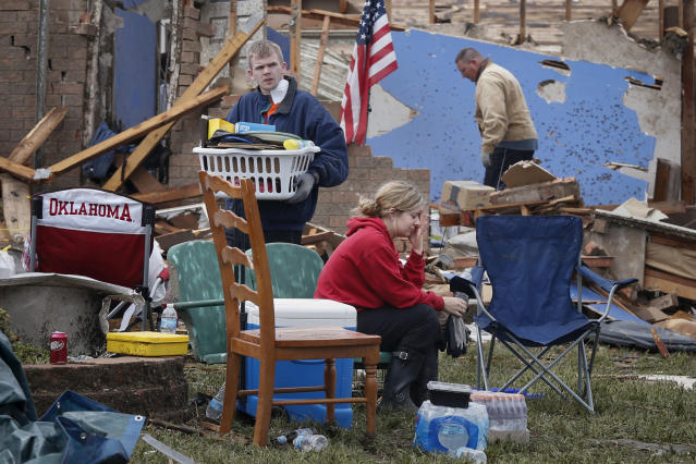Resident Taylor Tennyson sits in the front yard as family members salvage the remains from their home which was left devastated by a tornado in Moore, Oklahoma, in the outskirts of Oklahoma City May 21, 2013. Rescuers went building to building in search of victims and thousands of survivors were homeless on Tuesday, a day after a massive tornado tore through a suburb of Oklahoma City, wiping out whole blocks of homes and killing at least 24 people. REUTERS/Adrees Latif (UNITED STATES - Tags: DISASTER ENVIRONMENT TPX IMAGES OF THE DAY) - RTXZVMP