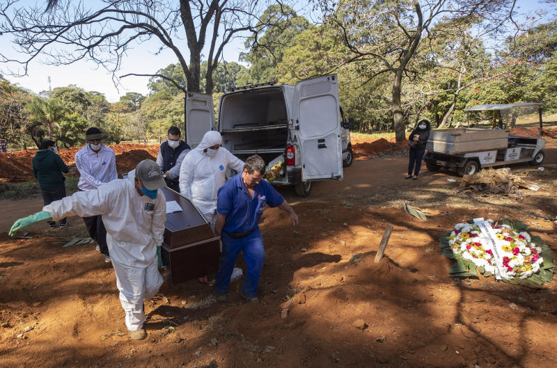 Cemetery workers in protective clothing carry the coffin of 58-year-old Paulo Cesar dos Santos, who died of COVID-19, at the Vila Formosa cemetery in Sao Paulo, Brazil, Thursday, May 28, 2020. (AP Photo/Andre Penner)
