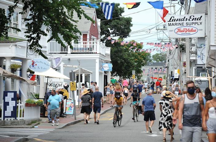 Visitors walk along Commercial Street in Provincetown this past summer. Many expect that masks and other COVID-19 protocols will remain in effect this coming tourist season.