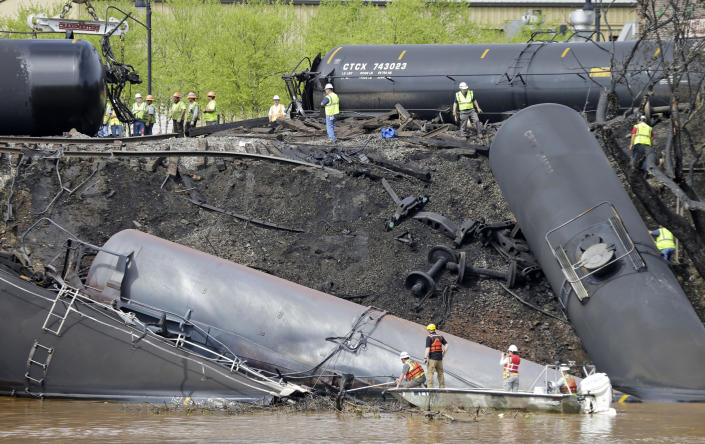 FILE - In this May 1, 2014, file photo survey crews in boats look over tanker cars as workers remove damaged tanker cars along the tracks where several CSX tanker cars carrying crude oil derailed and caught fire along the James River near downtown Lynchburg, Va. Inspectors have found almost 24,000 safety defects over a two-year period along United States railroad routes used to ship volatile crude oil. Data obtained by The Associated Press shows many of the defects were similar to problems blamed in past derailments that caused massive fires or oil spills in Oregon, Virginia and Montana. (AP Photo/Steve Helber, File)