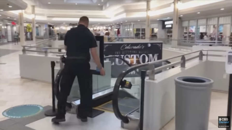 A screenshot from the CBS News Denver story showing a policeman blocking off the top of an escalator in the shopping centre.