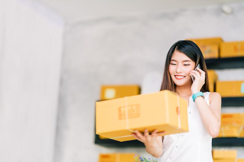 A smiling woman holds up a box and talks on her cell phone.