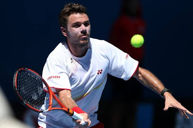 Stanislas Wawrinka of Switzerland makes a forehand return to Andrey Golubev of Kazakhstan during their first round match at the Australian Open tennis championship in Melbourne, Australia, Monday, Jan. 13, 2014.(AP Photo/Rick Rycroft)