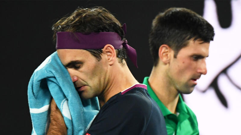 Roger Federer wipes his face with a towel as he passes Novak Djokovic.