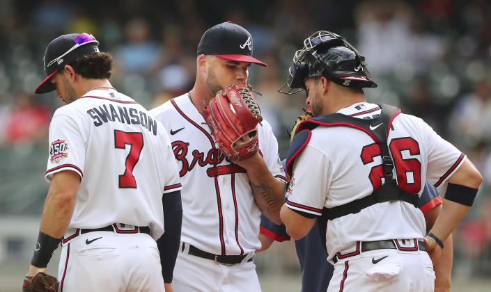 Atlanta Braves starting pitcher Bryse Wilson confers with catcher Stephen Vogt and Dansby Swanson during the first inning against the San Diego Padres in the second game of a baseball doubleheader Wednesday, July 21, 2021, in Atlanta. (Curtis Compton/Atlanta Journal-Constitution via AP)