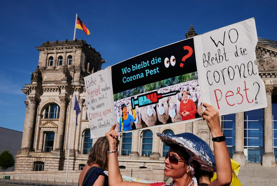 """dpatop - 31 July 2020, Berlin: A demonstrator holds up a sign saying """"Where is the Corona Plague?"""" In front of the Reichstag, the rally """"Democratic Resistance"""" """"for the restoration of constitutional democracy"""" took place. Photo: Annette Riedl/dpa (Photo by Annette Riedl/picture alliance via Getty Images)"""